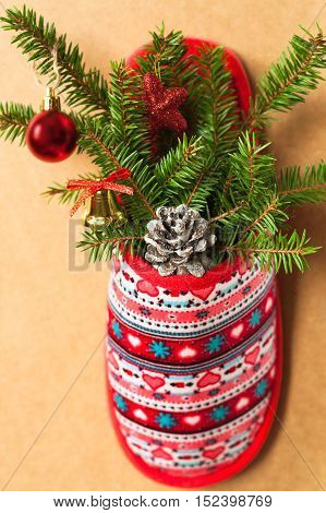 Christmas Pine Cone Decorative Balls And Fir-Tree Branches In Red Slipper With Patterns On Background. Close-Up. Christmas Tree With Decorations In Slipper.