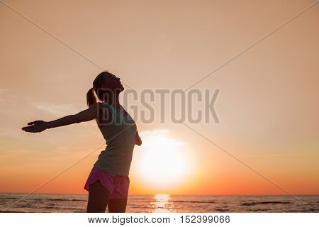 Happy woman after workout standing in the sunset
