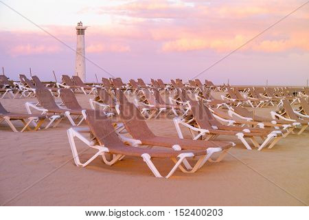 View on the beach Playa de Morro Jable with sunbeds on the sunset. Location Fuerteventura Spain.