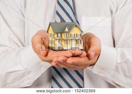 Men's Cupped Hands Holding a Model of a House - Close Up