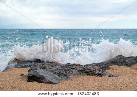 Lumpy sea at cloudy day. Seascape with rocky stones and splashes in the foreground
