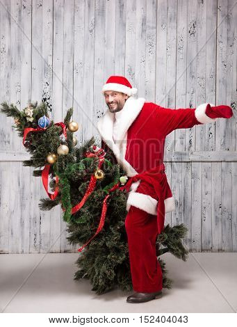 Picture of Bad Santa Clause riding on New Year Tree or Eve in studio. Happy man in Santa Clause clothes playing with New Year Eve.