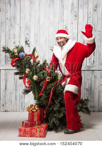 Picture of Bad Santa Clause waving to everybody whileriding on New Year tree iolated on white background. New Year concept.