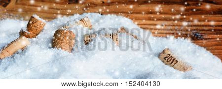 Bottle corks new year 2017 in snow in front of a wooden wall