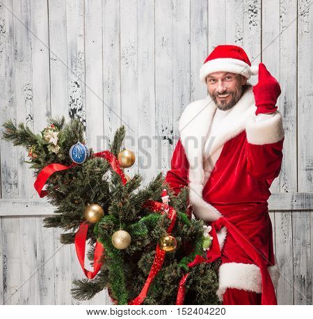Portrait of happy smiling Bad Santa Clause showing middle finger white riding on New Year Eve or tree isolated on white background in studio.