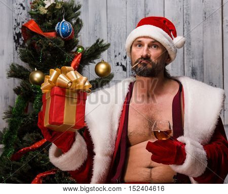 Portrait of naked Bad Santa Clause holding gift or present infront of him and looking at camera. Bearded Santa Clause near New Year Eve or tree.
