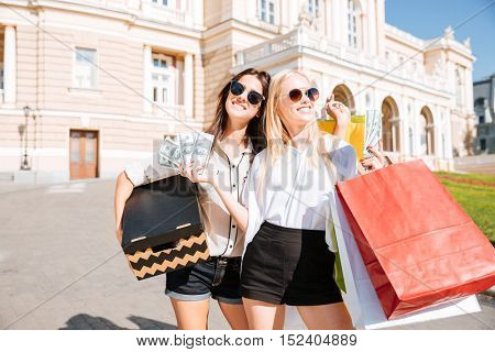 Two attractive young women holding shopping bags and smiling while standing outdoors
