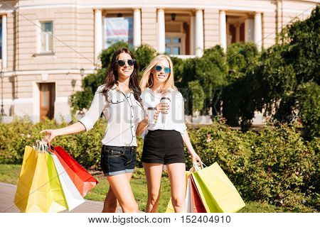 Two happy women with shopping bags walking outdoors