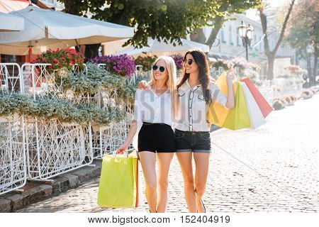 Beautiful women with shopping bags in the city walking in the street