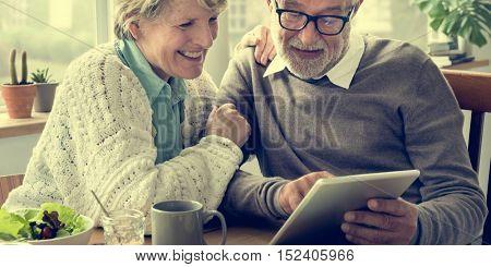 Senior Adult Holding Tablet Reading Concept