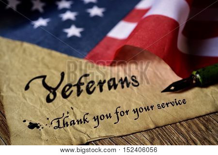 the text veterans than you for your service written in a piece of paper with a nib pen and a flag of the United States, on a rustic wooden background