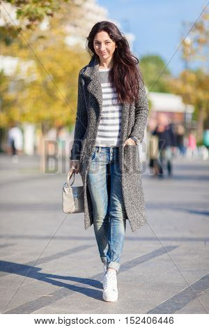 Beautiful stylish woman in blue jeans, trendy shoes and cozy trench coat walk in fall city park. Autumn outdoor lifestyle. Happy woman enjoy the fall. Street style, trendy outfit. Fall woman portrait