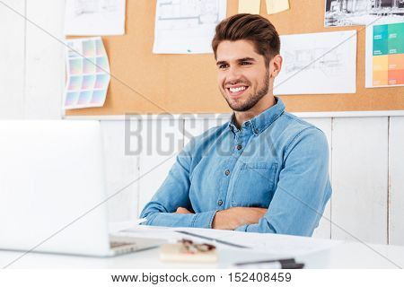 Confident smiling happy businessman sitting at the table with arms folded at the office