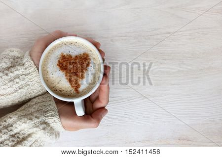 frothy cappuccino with heart pattern in hand and dressed up warm sweater top view / love warms