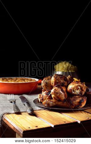Close view of grilled chicken legs, knife, and fork mash potatoes, pumpkin pie on a table on a black background. Dark photo. Vertical shot