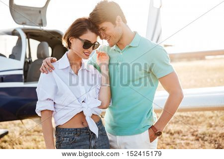 Beautiful young couple standing and hugging near small airplane