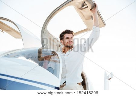 Cheerful young man pilot getting out of the plane after landing