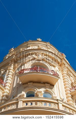 old corner building with stone balconies against a sky.