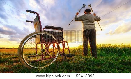 Miracle recovery: Old man gets up from wheelchair and raises hands up. Shot in a meadow. Recovery concept