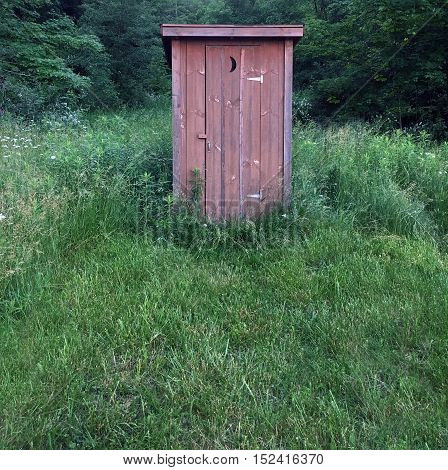 Rustic wooden outhouse in a grassy field.
