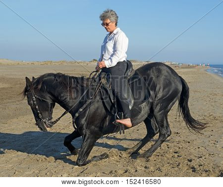 horsewoman making dressage with her stallion on the beach