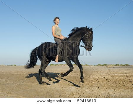 horse woman galloping with her black stallion on the beach