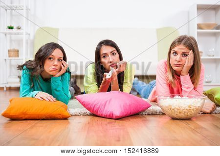Three friends are watching movie on TV at home.