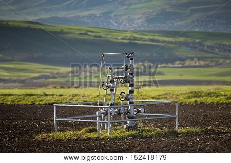 Natural gas wellhead in a meadow of green grassland field