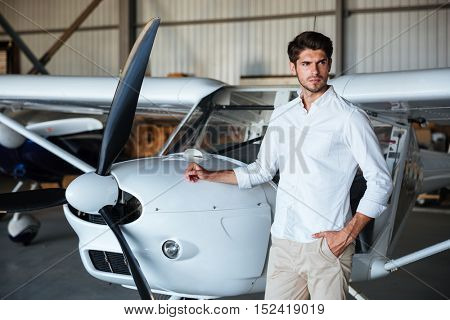 Portrait of attractive young man standing near small aircraft