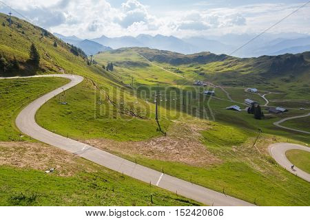 KITZBUEHEL, AUSTRIA - SEPTEMBER 2016 : People, cars on Panoramastrasse scenic road, leading up to Alpenhaus with blurred cable cars, mountains background in Kitzbuhel, Austria on September 27, 2016