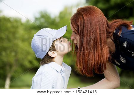Nice white boy kiss his beautiful young mother on spring sunny garden. Portrait of boy with mother. Happy family in sunny day. Mother and sun spend leisure time activities in nature. Woman kiss her son.