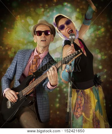 Rockabilly couple having fun playing the guitar and singing in front of colorful background
