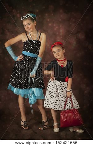 Rockabilly girls posing in 1950's style clothing in front of colorful background