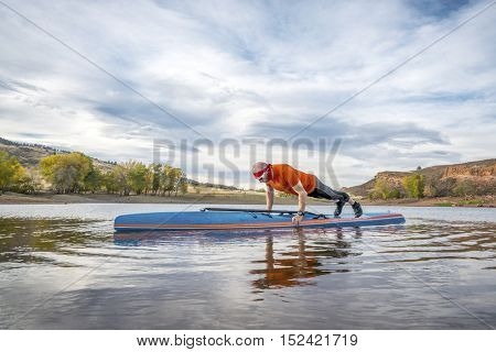 A senior male exercising (pushups and planks) on a stand up paddleboard, a calm mountain lake in fall colors