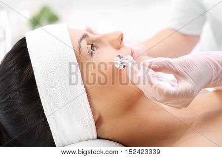 Face skin. Microdermabrasion. The woman in the beauty salon for the treatment mezotrrapii with the use of micro needle roller.