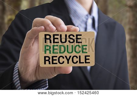 Businessman holding businesscard message recycle reduce reuse.Environmental concept recycle reduce reuse.