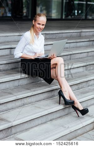 Full length portrait of a blonde businesswoman typing on laptop whie sitting on the stairs outside