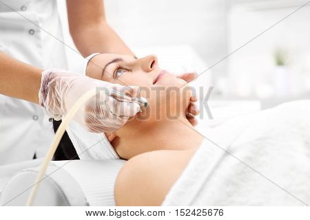 Beautiful neckline, microdermabrasion. Relaxed woman during a microdermabrasion treatment in beauty salon
