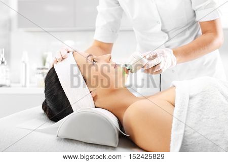 The woman's face during a facial at a beauty salon Ultrasound infrared light cosmetic treatment for the face