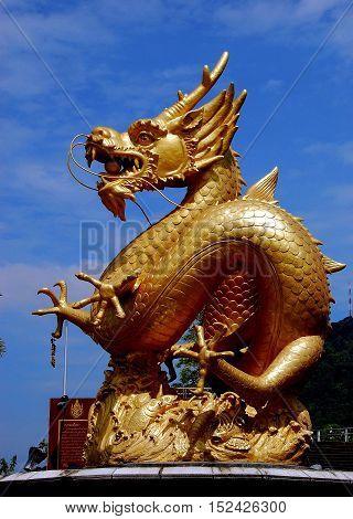 Phuket City Thailand - January 8 2011: A giant gilded dragon fountain dominates Queen Sirikit Park on Krabi Road *