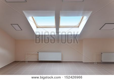 Modern interior of attic room with a sloping ceiling and skylight.
