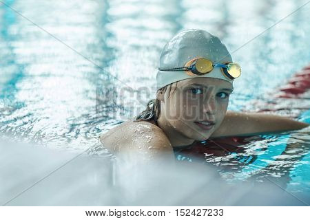 Swimmer child. Portrait of swimming child athlete in glasses after training in waterpool.