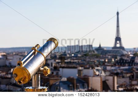 Touristic telescope overlooking Eiffel Tower from the roof of department  store. Paris, France