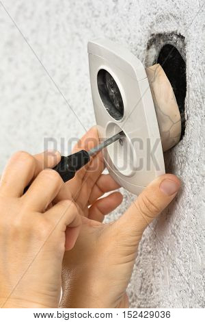 hand of an electrician dismantling broken wall electric socket