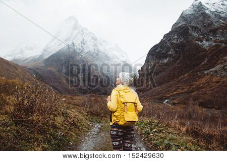 Young woman with backpack trekking in mountains. Cold weather, snow on hills. Winter hiking.