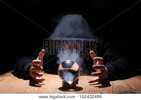man in a black hood with cristal ball summon evil