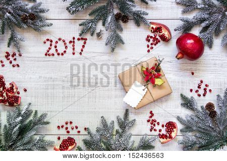 On the frame perimeter scattered branches of Christmas tree, pomegranates whole and broken, seeds, number 2017 and gift box on white wood background. Gift New Year's card background. Top view.