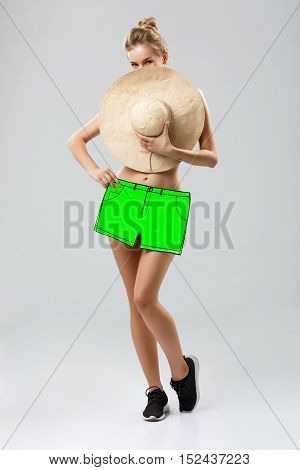 Attractive flirty girl covering with big hat and fake shorts over white background. Copy space.