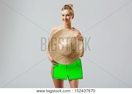 Attractive flirty girl smiling, covering with big hat and fake shorts over white background. Copy space.