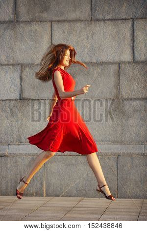 Full length portrait of attractive elegant young woman in a red dress jumping on the sidewalk on stone wall background